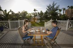 Young couple having coffee on terrace at holiday resort Stock Photos