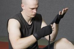 Male boxer wrapping strap around hand - stock photo