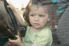 Young girl sitting in driver's seat of car Stock Photos