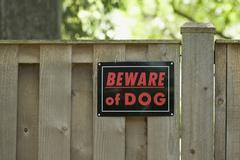 Beware of dog' sign on wooden fence Stock Photos