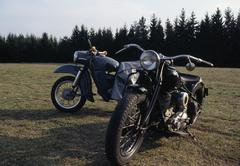 Two motorcycles parked on grass near woods Stock Photos