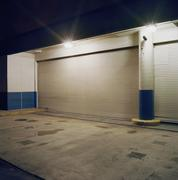 Floodlights above rolling garage doors at loading dock - stock photo