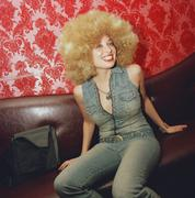 Young woman sitting on bench wearing blond afro wig Stock Photos