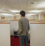 Young man looking over empty office cubicles - stock photo