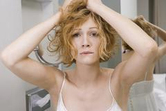 Stock Photo of Woman in bathroom tearing her hair out