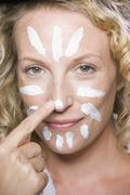Stock Photo of Woman applying moisturizer to her face