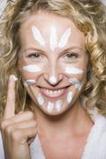 Woman applying moisturizer to face Stock Photos