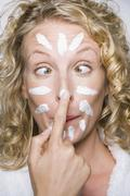 Stock Photo of Woman applying moisturizer with cross-eyed expression