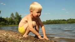 Little boy playing on the shore of the lake. Water Recreation Stock Footage