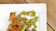 Stock Video Footage of chicken garnished with green sweet peas and red hot pepper