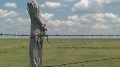 Wind turbines on prairie horizon behind old fence Stock Footage
