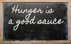 expression - hunger is a good sauce - written on a school blackboard with cha - stock photo