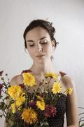 Young woman looking at bunch of flowers - stock photo