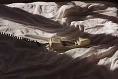 Telephone receiver off the hook on a bed Stock Photos