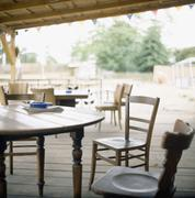 Chairs and tables on wooden patio Stock Photos