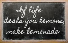expression - if life deals you lemons, make lemonade - written on a school bl - stock photo