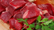 Fresh uncooked beef meat slices over wooden cutting board Stock Footage
