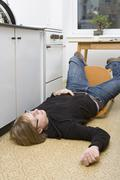 Young man lying on the ground after falling back in a chair - stock photo