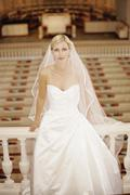 Bride sitting on railing in church stall Stock Photos