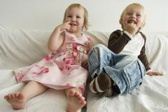 Brother and sister sitting on sofa and laughing Stock Photos
