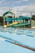 Empty swimming pool and water slides Stock Photos