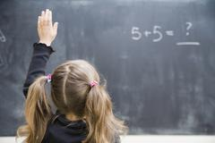 Girl in classroom with raised hand Stock Photos