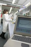 Stock Photo of Laptop on bench and technician measuring solution with pipette in a laboratory