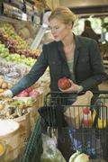 Woman choosing fruit and vegetables in supermarket Stock Photos