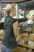 Woman buying bread at counter - stock photo