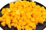 Stock Photo of orange tasty pumpkin blocks on black plate
