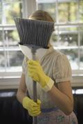 Woman holding broom in front of her face - stock photo