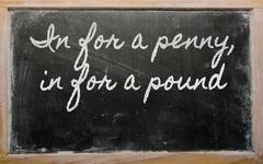 expression -  in for a penny, in for a pound - written on a school blackboard - stock illustration
