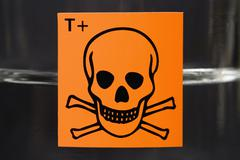 Toxic substance label with skull and crossbones on glass flask containing liquid - stock photo