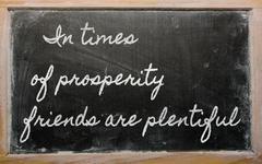 Expression -in times of prosperity friends are plentiful - written on a schoo Stock Photos
