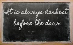 expression -  it is always darkest before the dawn - written on a school blac - stock illustration