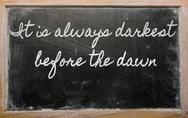 Stock Illustration of expression -  it is always darkest before the dawn - written on a school blac