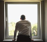 Businessman looking out a window Stock Photos