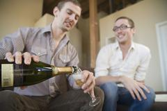Two men drinking champagne together Stock Photos
