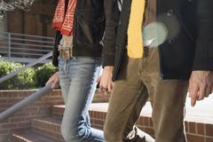 Midsection view of two gay men holding hands - stock photo
