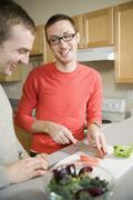 Two men preparing vegetables in kitchen together - stock photo