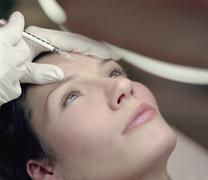 Woman receiving a Botox injection - stock photo