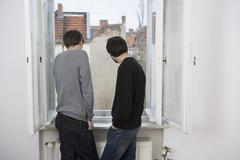 Two young men looking out of window Stock Photos