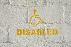 Disabled parking sign on a brick wall Stock Photos