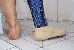 Low section of man showering with prosthetic leg - stock photo