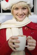 Young woman wearing a Santa hat and holding a mug of hot chocolate Stock Photos