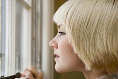 Young woman looking out a window Stock Photos