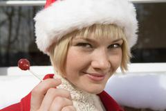Young woman wearing a Santa hat and holding a lollipop Stock Photos