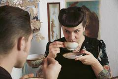 Young rockabilly couple drinking tea together - stock photo