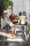 Woman washing vegetables at sink, with tattooed arm Stock Photos