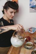 Nuori rockabilly nainen kaataa teetä Kuvituskuvat